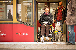 A woman in a wheelchair is accompanied by a dog in the train.